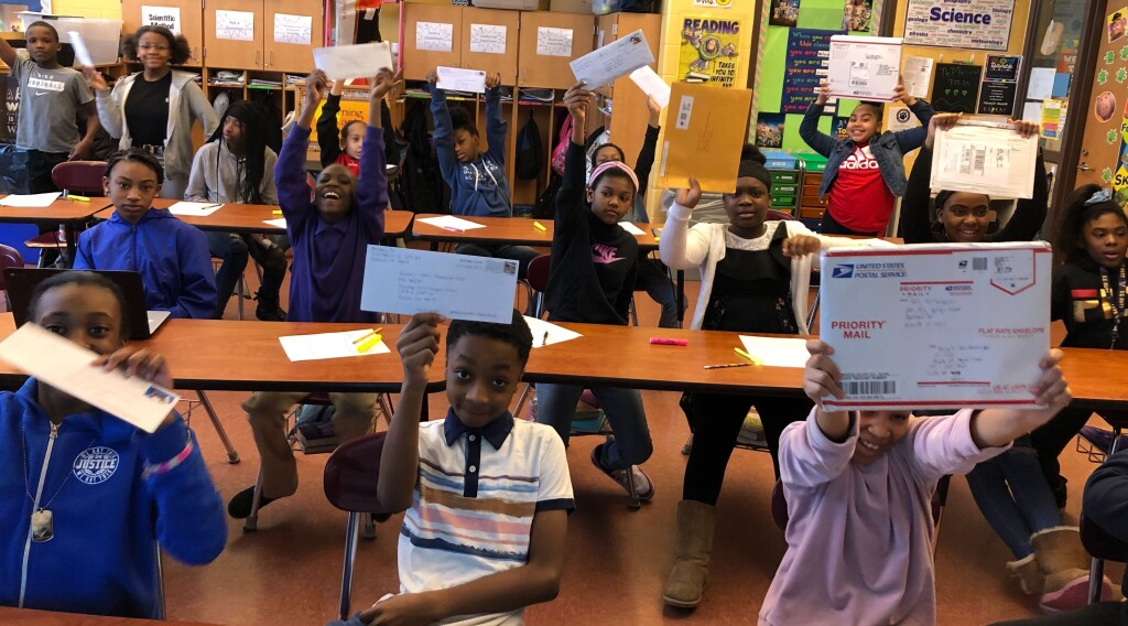 Students sitting at desks in a classroom excitedly hold up their letters.