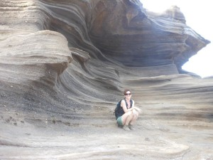 """On a field trip looking at ash deposits on Oahu, Hawaii.  White pieces of rock visible in the gray ash layers behind me are chunks of coral reef ripped up by the explosive eruptions that led to these deposits."""