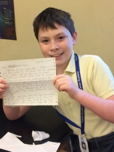 Boy in yellow polo shirt smiling and holding a letter