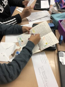 Student wearing a black sweatshirt is holding a handwritten pen pal letter. On their desk is an opened envelope and an envelope addressed to their pen pal.
